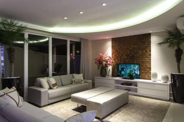 Sala com sofá bege e decoração clássica