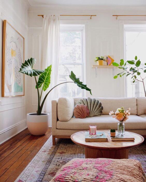 Sala com sofá bege claro com almofadas em formato de concha