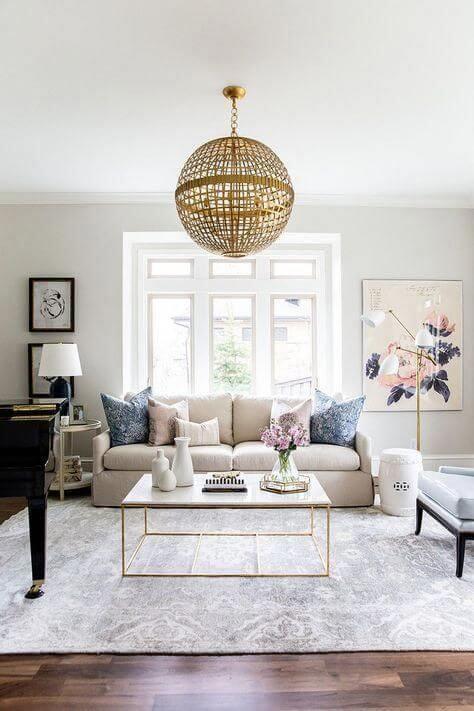 Sala de estar com sofá bege e almofadas azuis