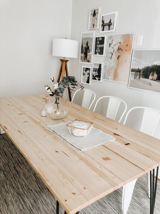 Sala de jantar com mesa de madeira rústica e cadeiras brancas