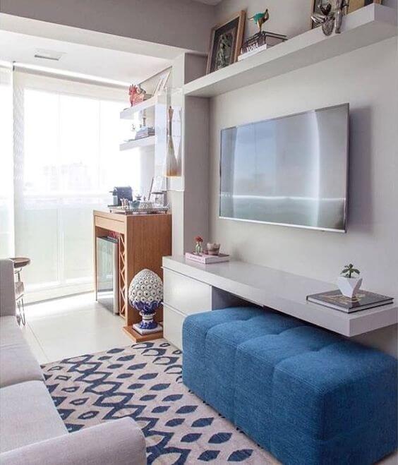 Sala pequena com painel para tv branco e puff azul