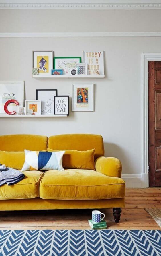 sofá para sala amarela decorada com prateleiras para quadros Foto Histórias de Casa