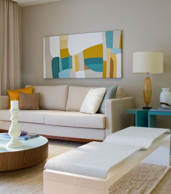 Sofá bege na sala de estar em tons de azul e amarelo