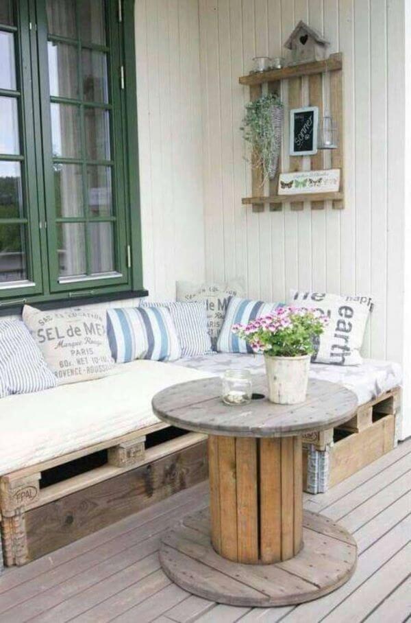 Varanda com sofá de palete com janela verde
