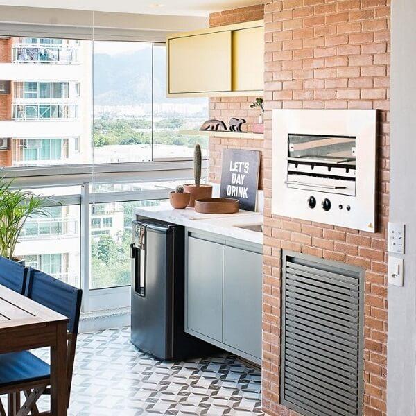 A churrasqueira para apartamento pode ser envolvida por uma parede de tijolinhos aparentes