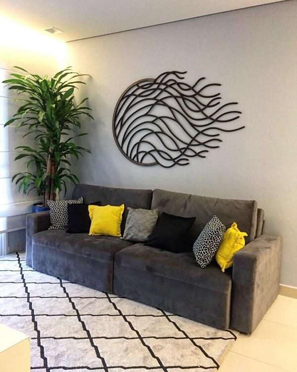 A escultura de parede complementa a decoração do cômodo