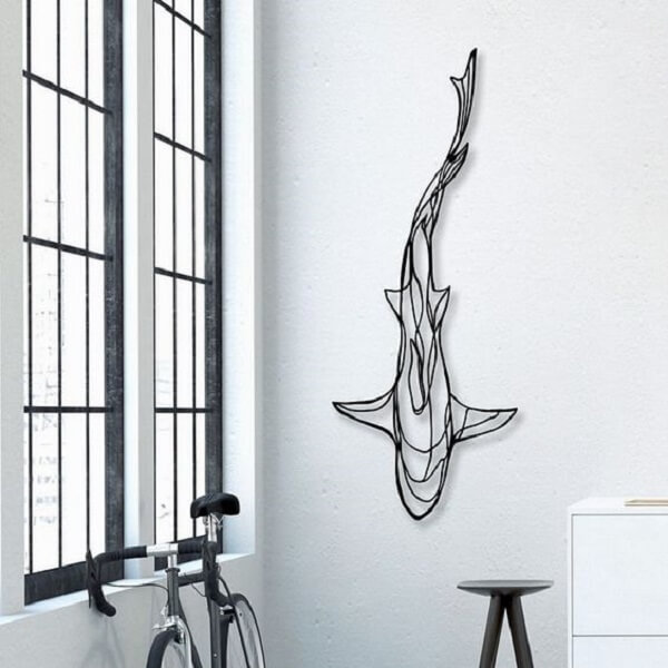 A escultura de ferro da parede forma a imagem de um tubarão