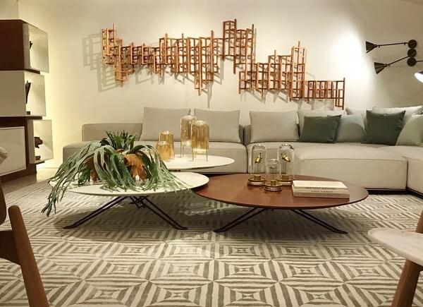 A escultura de parede metal dourada se destaca na sala de estar
