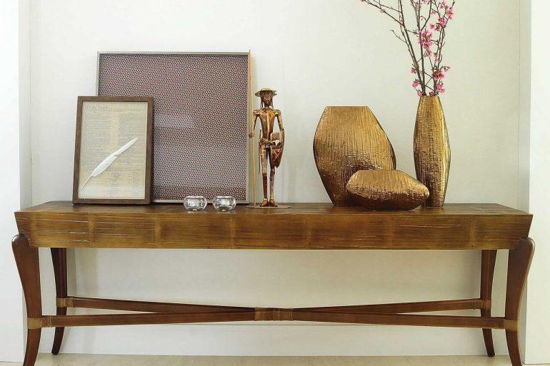 Aparador de madeira com quadros e vasos em cima