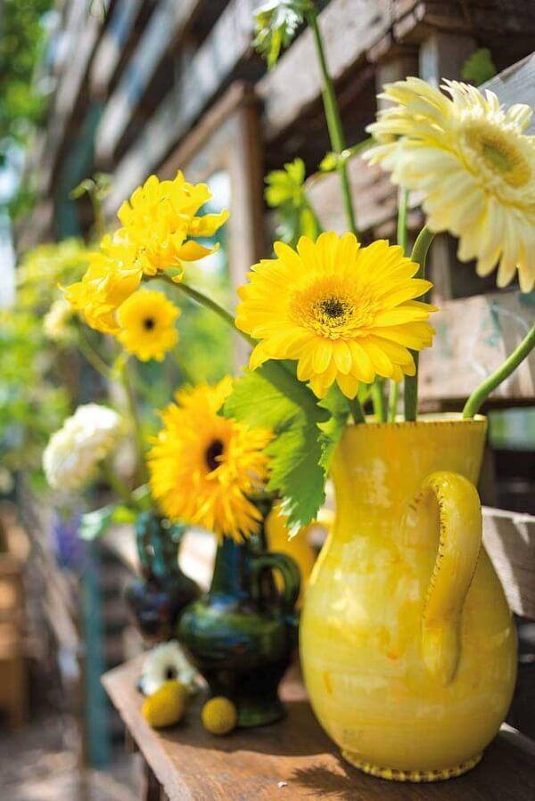 As flores amarelas de gérbera no vaso trazem aconchego para a decoração