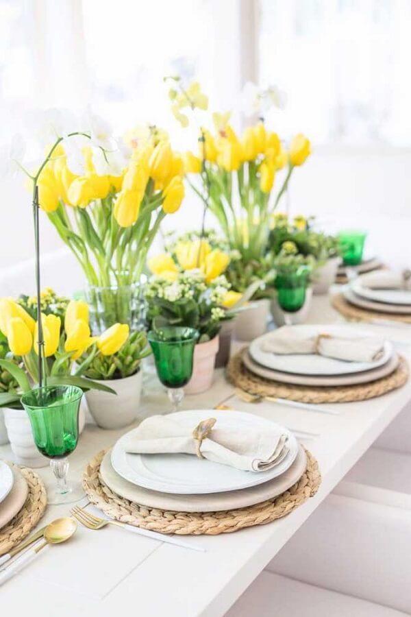 As flores amarelas de tulipa alegram o centro da mesa