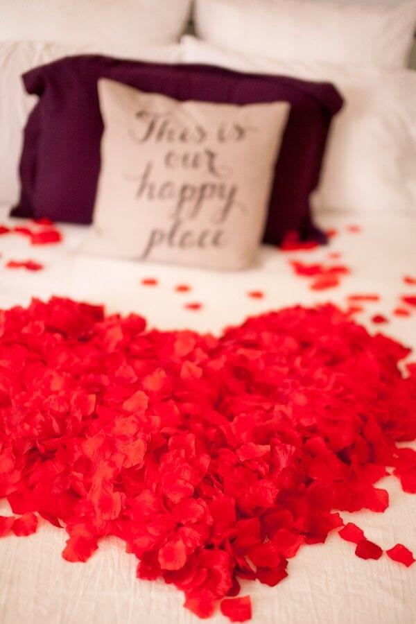 As pétalas de rosas podem formar um lindo coração sobre a cama
