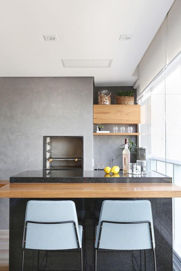 Bancada de granito preto e cadeiras estofadas complementam a decoração da varanda