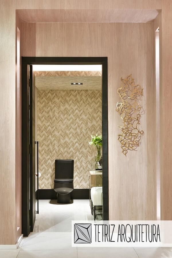 Entrada do lavabo com escultura de parede metal dourada