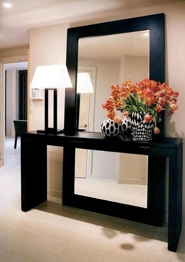 O aparador preto tem o mesmo acabamento da moldura do espelho