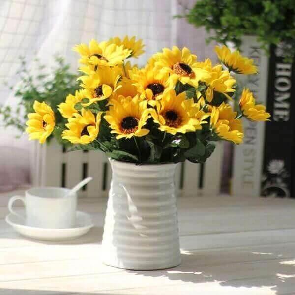O vaso branco traz destaque para as flores de girassol