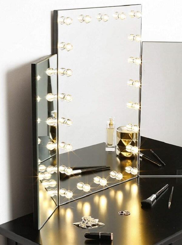 Penteadeira camarim com espelho apoiado na bancada, sem moldura e com mini lâmpadas