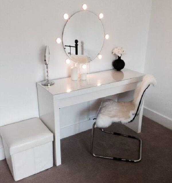 Penteadeira camarim com luzes na parede contornando o espelho