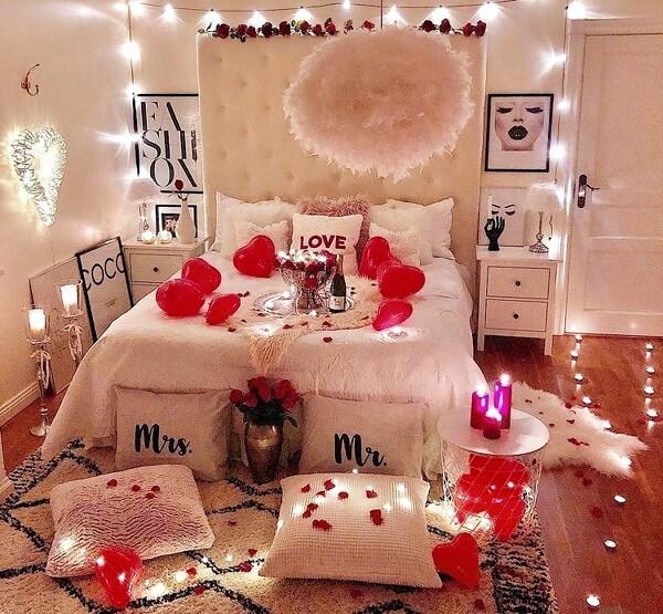 Quarto decorado para dia dos namorados com pétalas, luzes e flores