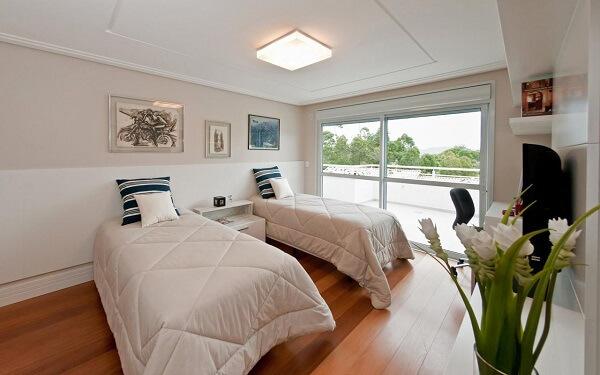 Quarto planejado com criado mudo branco e piso de madeira