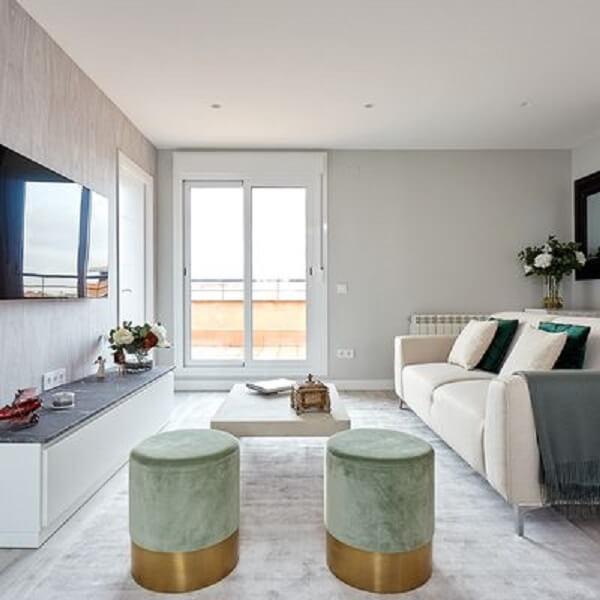 Sala de estar com tapete e sofá com mantas e almofadas