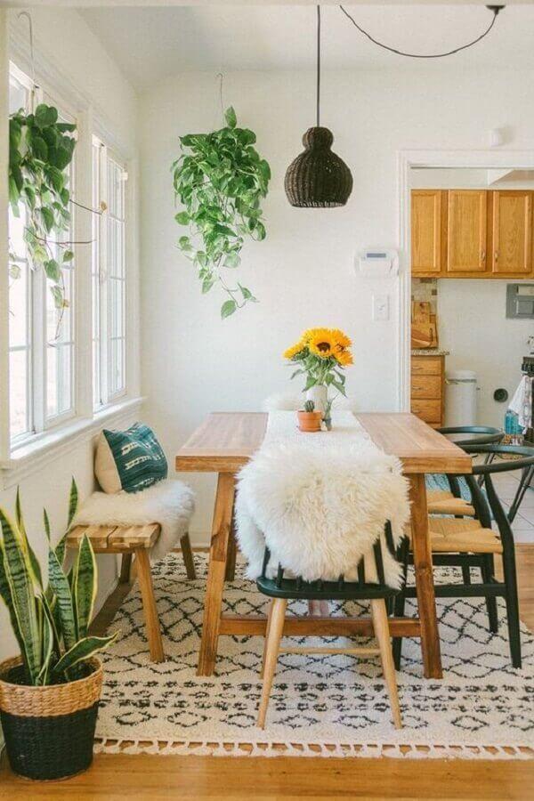Sala de jantar decorada com plantas pendentes e móveis de madeira Foto ArchiZine
