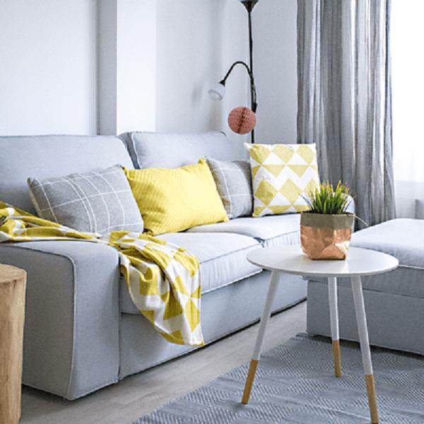 Sofá de cor neutra com almofadas e manta colorida reflete em um dos truques para melhorar a decoração da casa
