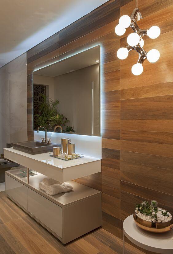 Banheiro com porcelanato amadeiro escuro e espelho iluminado ao redor