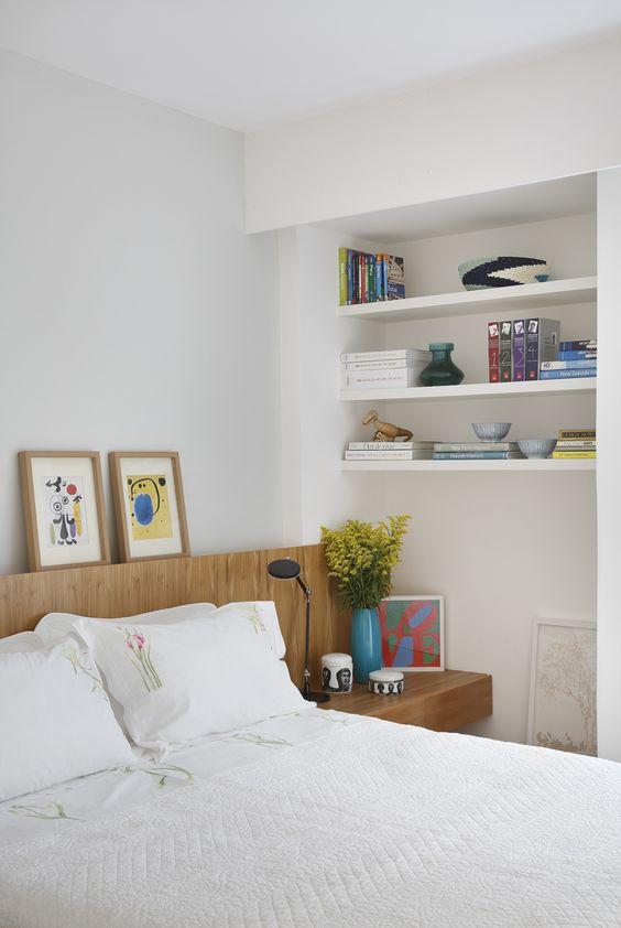 Cabeceira de madeira com criado mudo e prateleiras no quarto