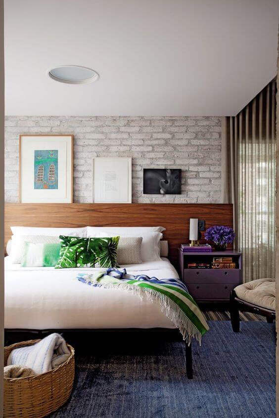 Cabeceira de madeira com papel de madeira de tijolinho e quadros apoiados