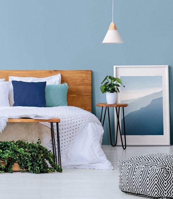 Quarto azul com cabeceira de madeira rústica
