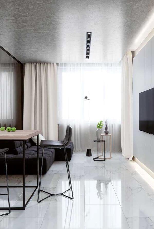 Sala iluminada com sofá preto e móveis estilo industrial