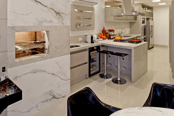 Cozinha com churrasqueira e revestimento de mármore