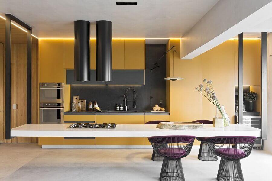 cozinha completa moderna decorada com armários planejados amarelos e ilha central grande com cooktop Foto Diego Revollo