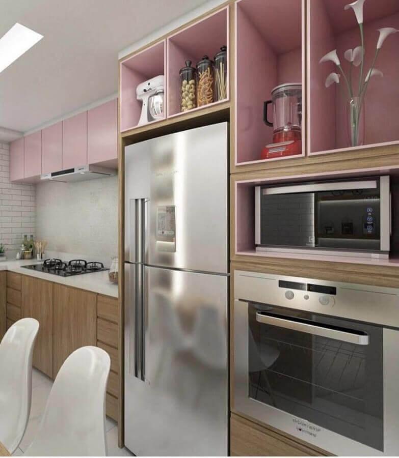cozinha completa planejada com armários cor de rosa e detalhes em madeira Foto ArchDaily
