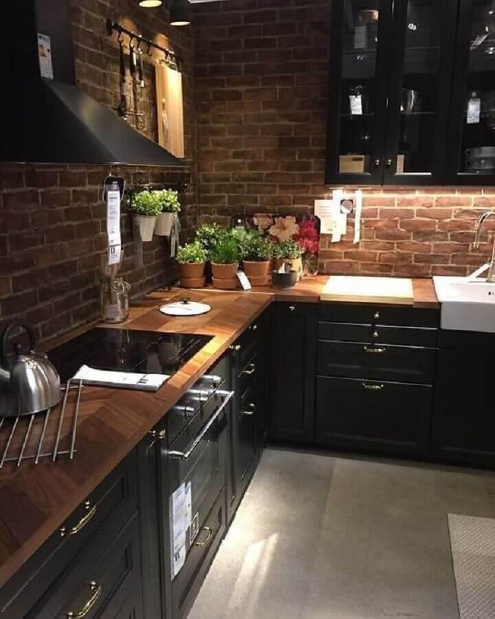 cozinha completa preta decorada com bancada de madeira e parede de tijolinho a vista Foto Sedsk Decor