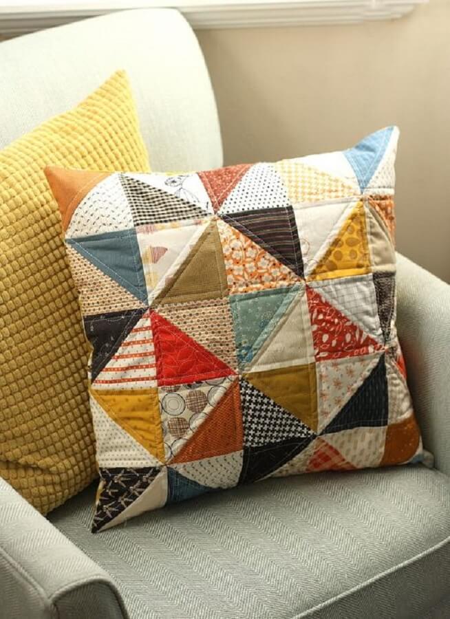 decoração com almofada de retalhos coloridos e poltrona cinza