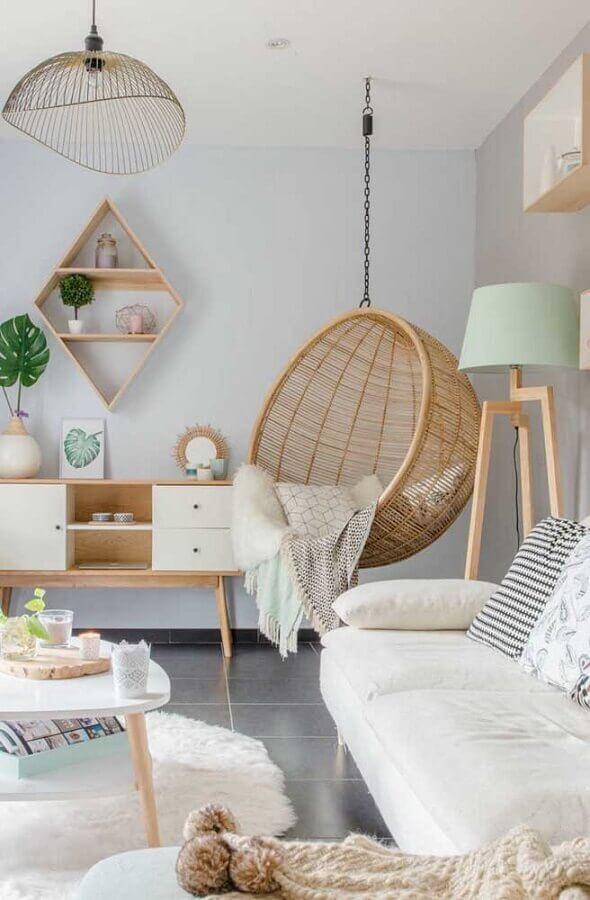 decoração em tons pastéis para sala com cadeira de balanço suspensa e abajur de madeira de chão Foto Pinterest