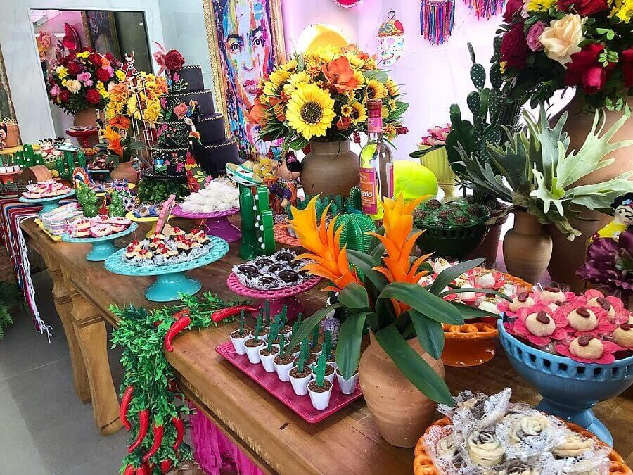 Mexican party decoration with flower arrangements and colorful dishes Foto Bello Toque