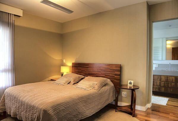 Cama com cabeceira de madeira no quarto de casal
