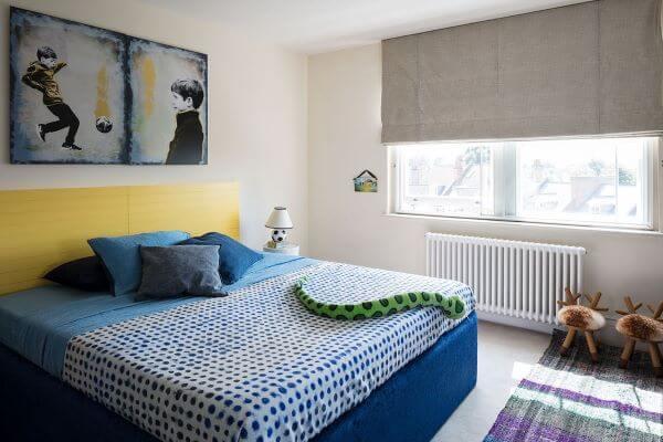 Quarto com cama box casal padrão azul e cabeceira amarela