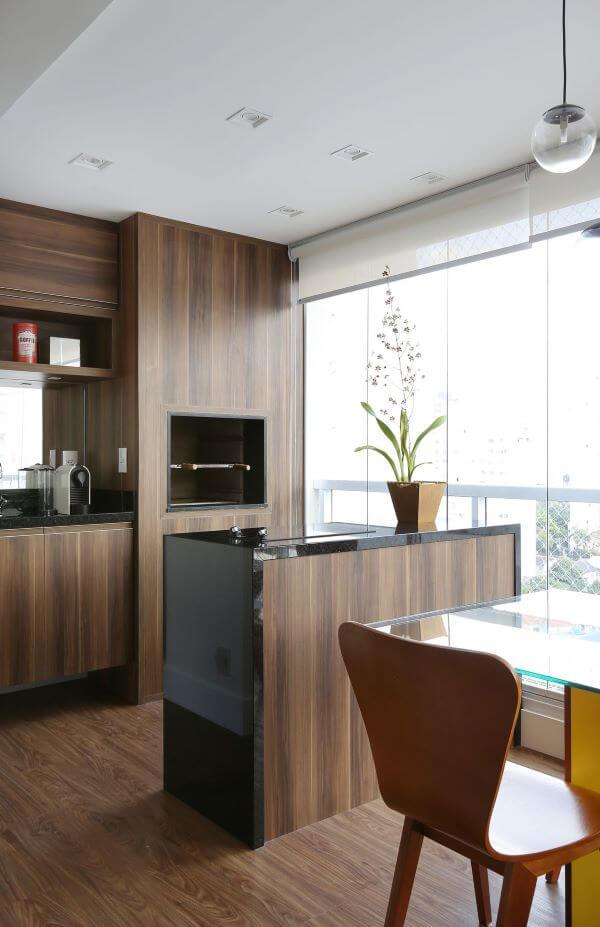 Churrasqueira elétrica na varanda moderna com revestimento de madeira