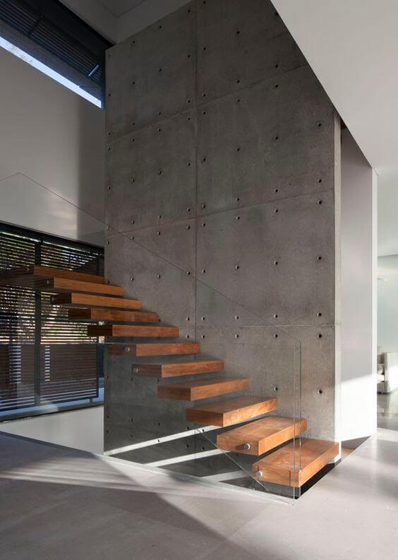 Escada vazada de madeira com guarda corpos de vidro