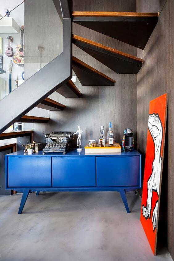 Decoração embaixo da escada com aparador azul
