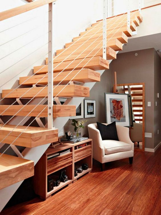 Escada vazada de madeira com poltrona embaixo da escada