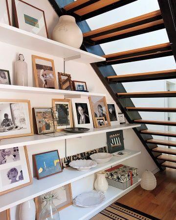 Decoração embaixo da escada vazada com prateleiras e porta retratos