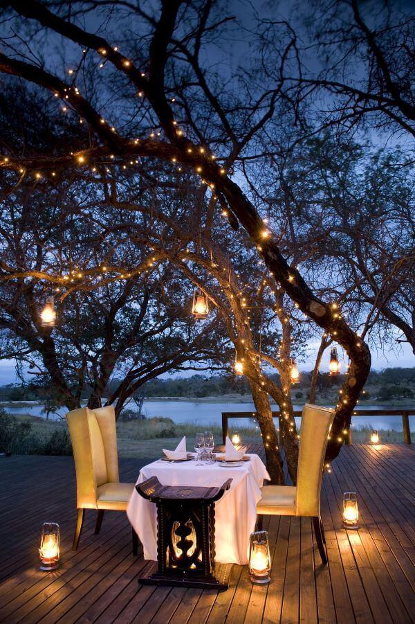 Mesa de jantar no jardim com decoração romântica e iluminada