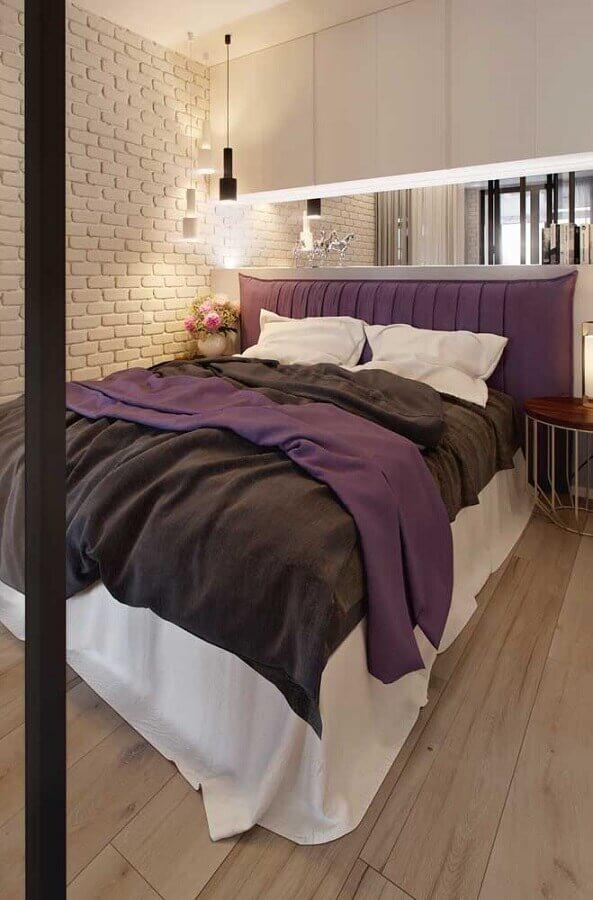 quarto de casal bonito decorado com cabeceira estofada roxa e parede de tijolinho branco Foto Archello