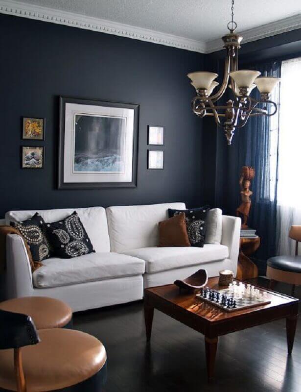 sala azul marinho decorada com sofá branco e móveis de madeira Foto LBL Lighting