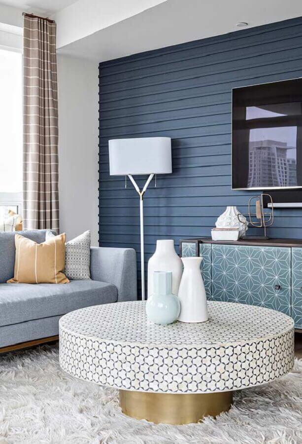 sala com parede azul decorada com sofá cinza e tapete felpudo branco Foto Kris Bristot